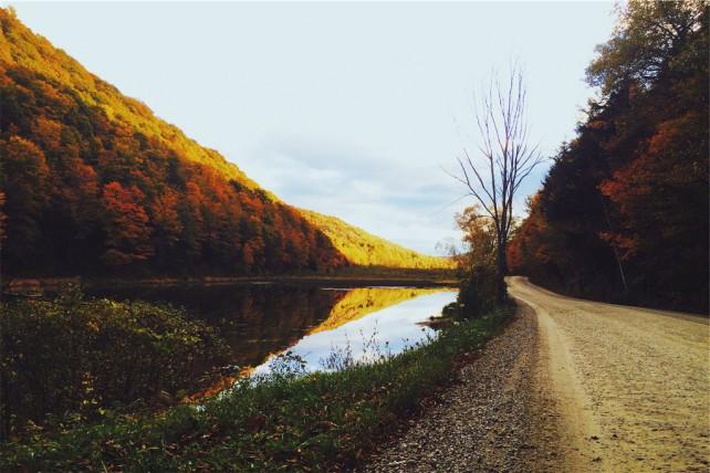 Foto einer Straße, die an einem Fluß entlangläuft. Links und rechts sind Herbstwälder im Bild.