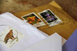 Foto von mehreren Briefumschlägen samt Briefmarken und Poststempel