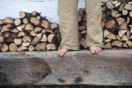 Michael steht auf einem Pressbalken - Scheitholz im Hintergrund. Nur seine Füsse sind zu sehen.