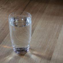 Foto eines Glases Wasser auf einem Holztisch.