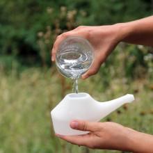 Foto einer Nasenspülkanne, die mit warmem Wasser befüllt wird.