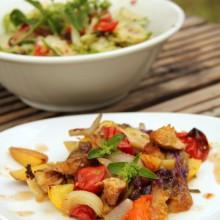 Foto von gebackenem Gemüse auf einem Teller, im Hintergrund eine Schüssel mit Salat.