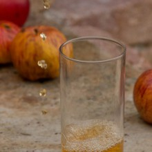 Foto von Apfelessig, der in ein Glas gegossen wird.