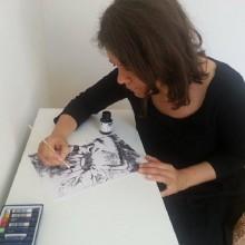 Foto einer Frau beim Tuschezeichnen.