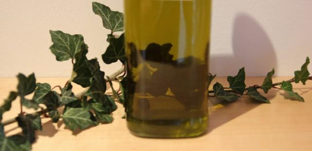 Foto einer Flasche mit Efeu-Ölauszug, hinter der eine Efeuranke liegt.