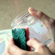 Foto von einem Glas, dessen Etikett gerade runtergeschrubbt wird.