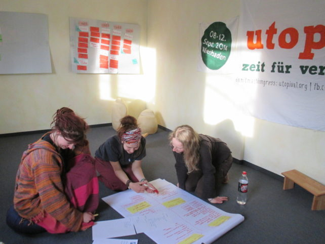 Drei Menschen, die gemeinsam in einen Planungsprozess involviert sind.
