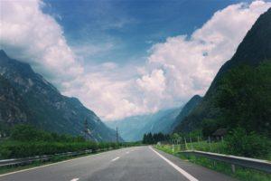 Foto einer Strasse, die geradeaus zwischen zwei Bergen hindurchführt.