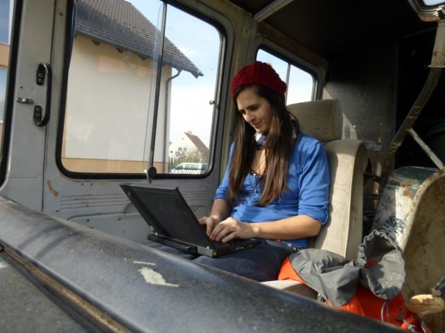 Foto von Lisa am Laptop auf dem Beifahrersitz des Busses