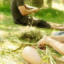 Foto von Frau beim Graskorbflechten