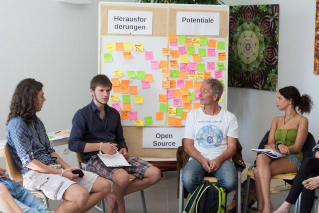 Foto einer kleinen Diskussionsrunde vor einem Flip Chart mit bunten Zetteln daran.