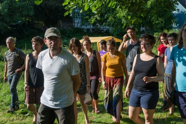 Foto einiger Teilnehmender des utopivals, die über das Gelände geführt werden und sich neugierig umsehen.