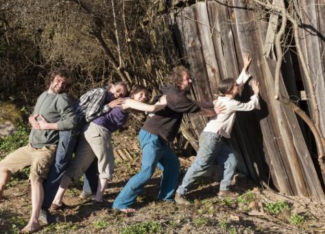 Foto von fünf Mitgliedern des Hofkollektiv Zwetschke, die so tun, als würden sie einen umstürzenden Holz-Stadl stützen.