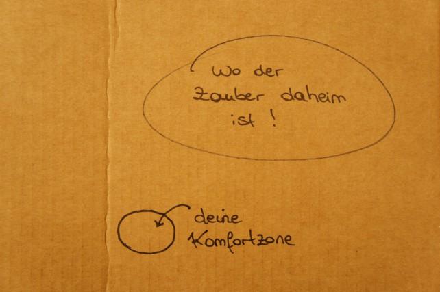 """Foto von einem Pappkarton mit der Aufschrift """"Deine Komfortzone"""" - """"Wo der Zauber daheim ist"""""""