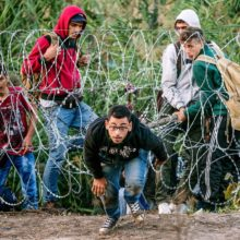 Foto eines Flüchtlings, der den Stacheldrahtzaun zwischen Serbien und Ungarn durchquert.