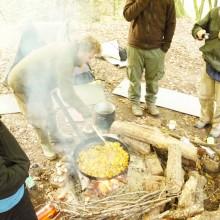 Martin bückt sich über die Pfanne und rührt das Essen am Lagerfeuer um.