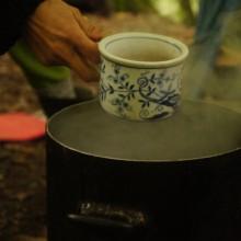 Eine Tasse wird in einen Topf mit dampfenden Tee getaucht.