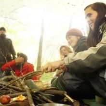 Frau hält einen Apfel an einem Stock über das Feuer.