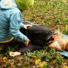 Frau liegt am Boden. Eine zweite Person bringt sie in die stabile Seitenlage.