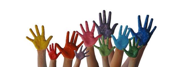 Viele weiße Hände, die winken und bunt angemalt sind.