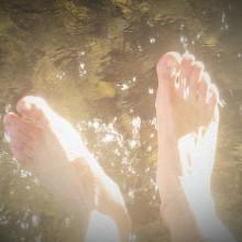 Füße, die im Flusswasser pritscheln.