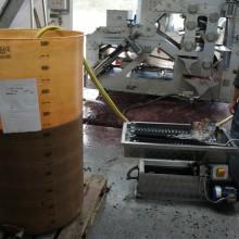 Ein gelber Plastikcontainer wird mit 355 Liter Traubensaft aufgefüllt.