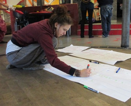 Pia auf dem Boden mit großem Bogen Papier und einen Stift in der Hand.