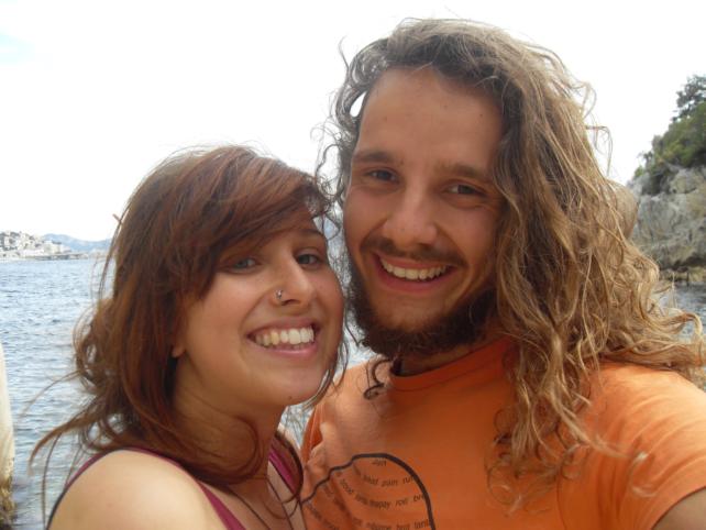Tobi und Pia lachen vor dem Meer in die Kamera
