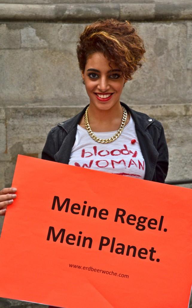 """Zu sehen ist eine Frau mit dem Schild """"Meine Regel. Mein Planet."""" in den Händen. Für den Gebrauch von Mondtassen und Stoffbinden!"""