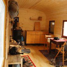 Küche, Holzofen, Esstisch und Garderobe im Bauwagen.