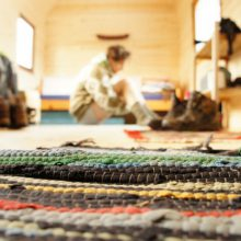 Detailaufnahme Teppich. Mann sitzt im Hintergrund.