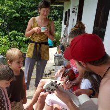 Foto von Kindern, die einer Gruppe von drei Menschen beim Ukulele-Unterricht zusehen