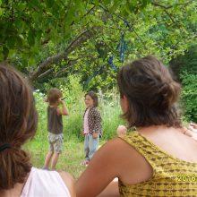 Foto von zwei Kindern, die sich unterhalten im Hintergrund. Im Vordergrund Erwachsene, die das beobachten, von hinten.