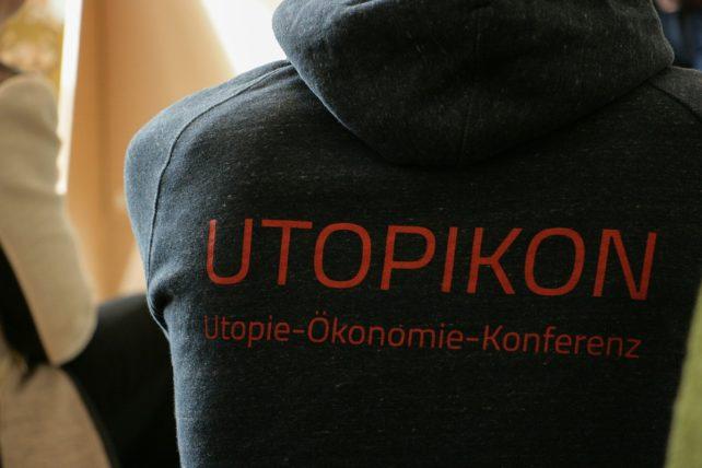 Foto des UTOPIKON Logos auf dem Rücken eines Pullovers - darunter steht: Utopie-Ökonomie-Konferenz