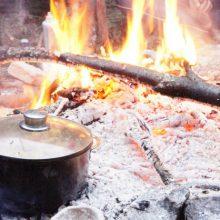 Angekohlter Topf steht im Lagerfeuer.