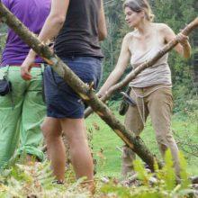 Menschen die ein Wildnisshelter bauen.