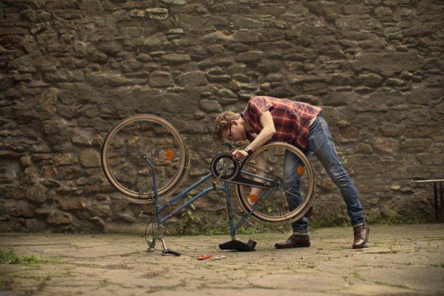 Geschenkidee Reparieren statt neu kaufen aus der Kampagne Zeit statt Zeug. Ein Mann repariert ein blaues Fahrrad.