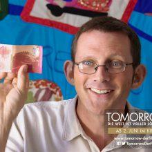 Szene aus dem Film Tomorrow: Rob Hopkins zeigt lächelnd einen Schein seiner Regionalwährung