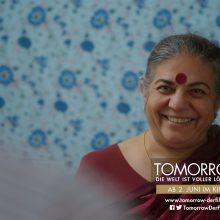 Szene aus dem Film Tomorrow: Vandana Shiva sitzt vor einer blauen Wand und lächelt.