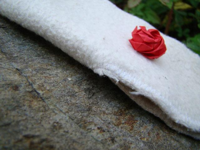 weiße Stoffbinde, Seitenansicht, mit kleiner roter Rose
