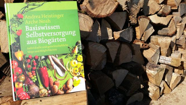 Foto des Buches Basiswissen Selbstversorgung aus Biogärten vor aufgestapeltem Holz