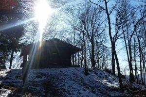 Berghütte im Schnee mit Sonnenlicht