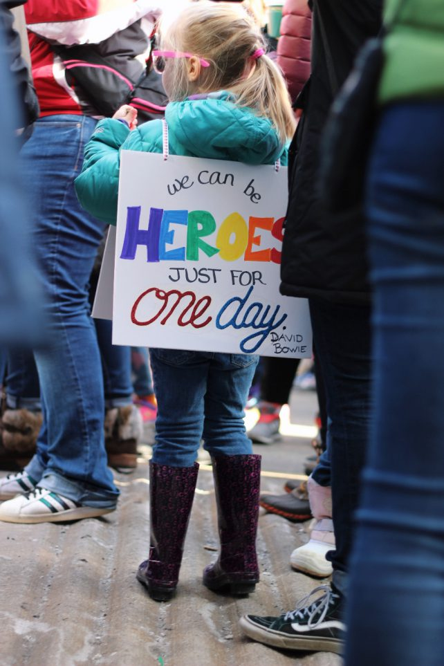 Foto eines Kindes von hinten auf einer Demo mit einem umgehängten Schild: We can be Heros just for one day.